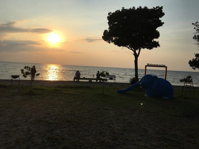 真玉海岸で夕日を見る人